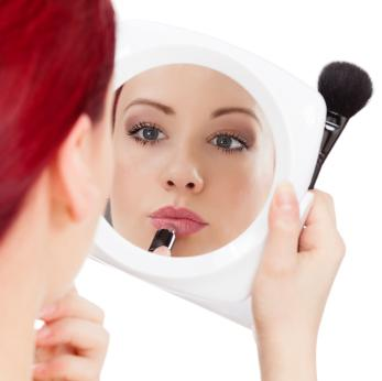 applying makeup in mirror