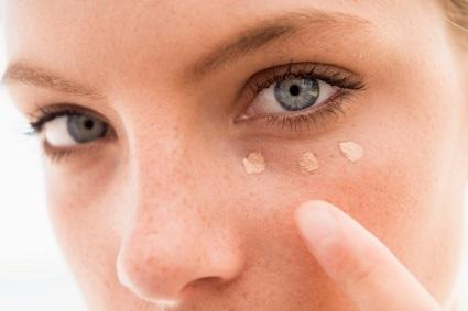 Woman applying eye concealer