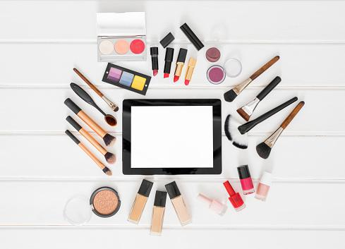 Makeup brushes and tablet on table
