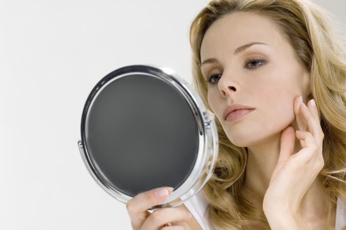 Woman using magnifying makeup mirror