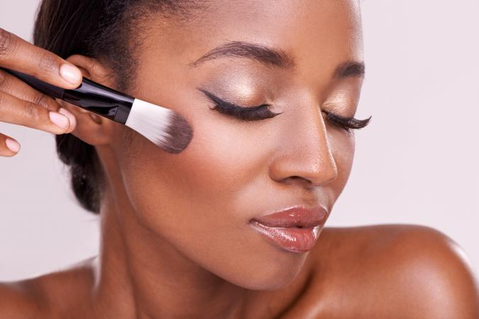 African American woman applying makeup