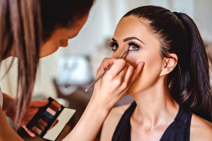Woman having eye makeup applied