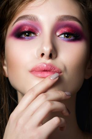 Closeup portrait of young beautiful woman with bright pink smokey eyes and lips