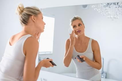 Woman applying makeup on her face