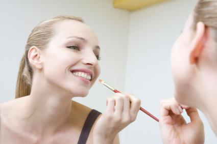 Woman applying highlighter to lips