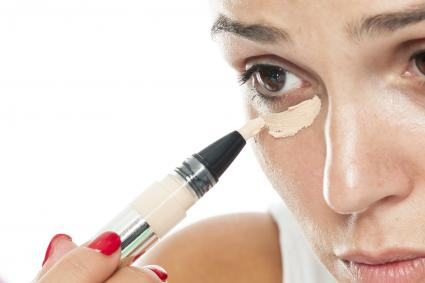 Women applying eye concealer