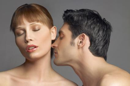 Man smelling a woman's neck