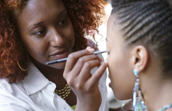 Makeup artist applying eye makeup on client