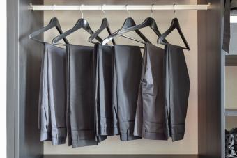 black pants hanging in wardrobe closet