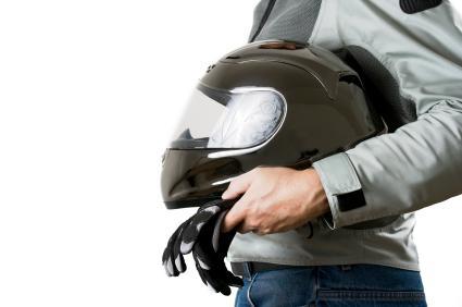 motorcyclist in gray jacket holding helmet