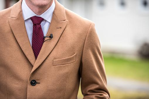 man wearing camel colored jacket
