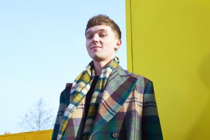 Fashionable young man in tartan coat