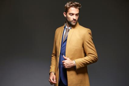 Handsome young businessman posing with overcoat Cancel Create