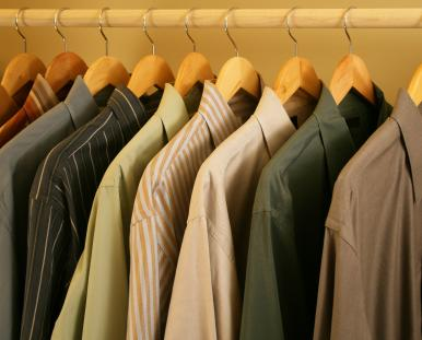 Nine men's shirts hanging in a closet