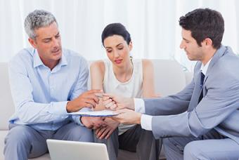 Couple filling out application with mortgage broker