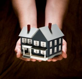 Hands holding model of a house