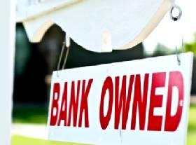 """Bank Owned"" for sale sign in yard"