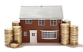 Small house flanked by stacks of coins