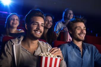 happy moviegoers eating popcorn in cinema