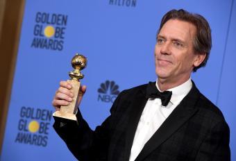 Hugh Laurie holding an award