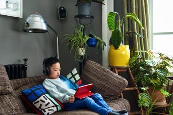boy wearing headphones watching movie on tablet