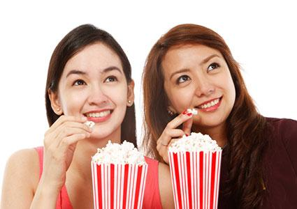 Two girls eating popcorn at the movies