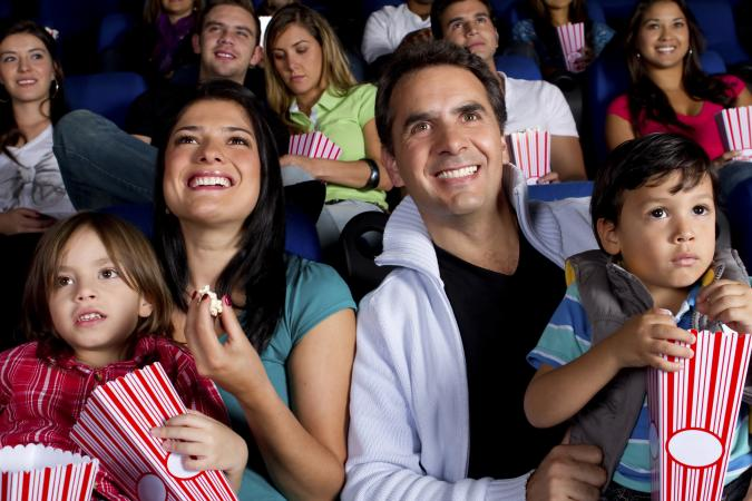 family enjoying movie at theater