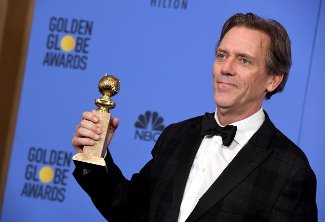 Hugh Laurie holding an award