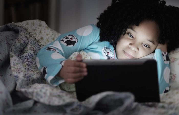 girl using digital tablet in bed