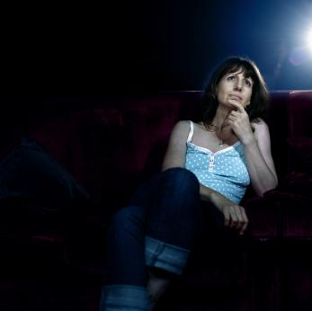 Woman watching a movie in a theater.