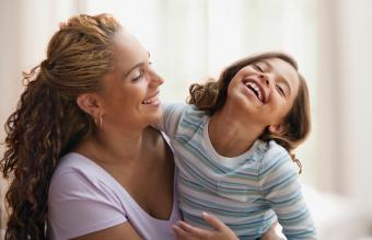 Madre abrazando y riendo con su hija