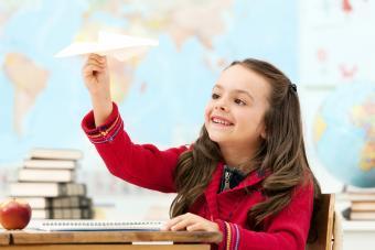 niña sosteniendo un avión de papel