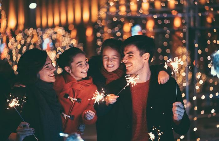Familia feliz con bengalas encendidas