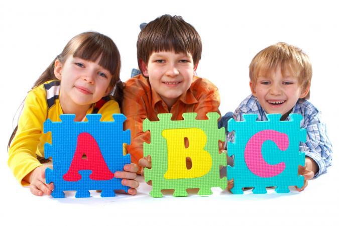 Niños con rompecabezas gigante del alfabeto