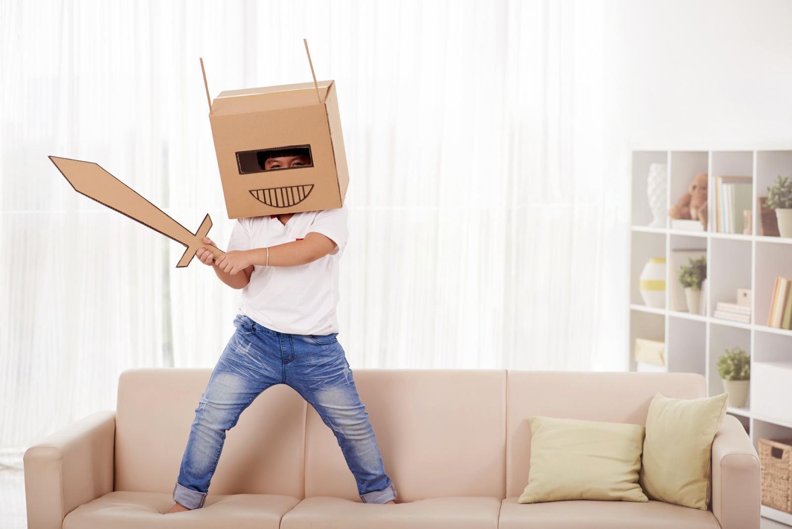 Niño jugando con cajas de cartón usando su imaginación