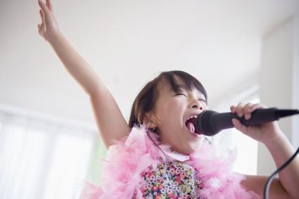 Niña cantando con un micro