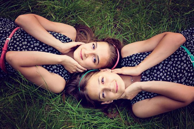 hermanas gemelas tumbadas en la hierba