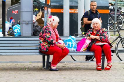 gemelos maduros sentados en un banco