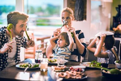 Familia de cuatro cenando y jugando