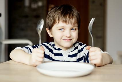 Niño feliz esperando la cena