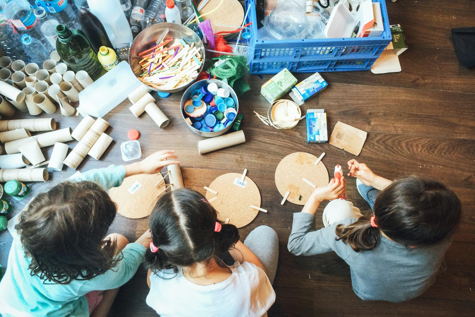 Niños haciendo manualidades con material reciclado