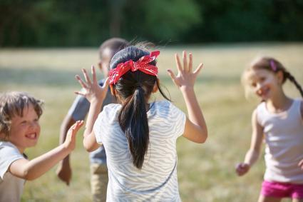 Grupo de niños jugando a un juego con una niña con los ojos vendados
