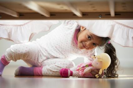 Niña con una muñeca en la mano buscando bajo la cama