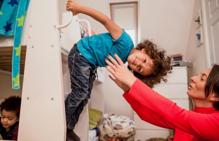 Niño inclinado hacia abajo con mamá listo para atraparlo