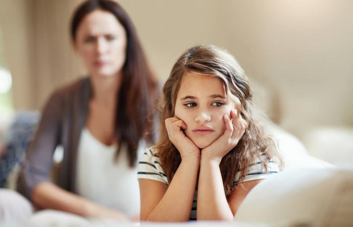Niña siendo reprendida por su madre en casa