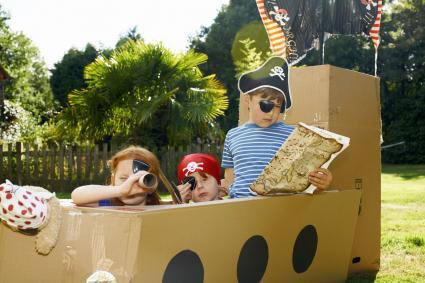 Niños en un barco de cartón buscando un tesoro