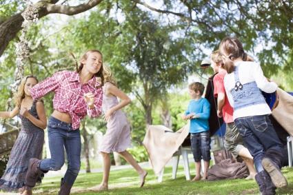 Niños corriendo en circulo en un jardín