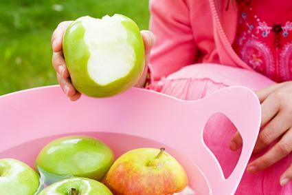 Manzanas flotando en un cubo de agua y una niña comiendo una