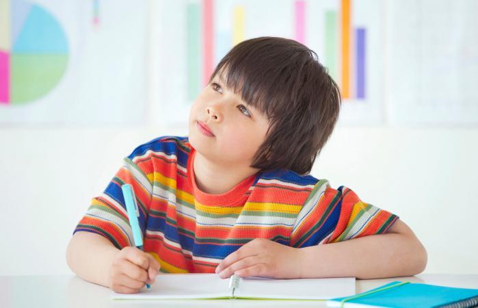 Niño sentado escribiendo en clase