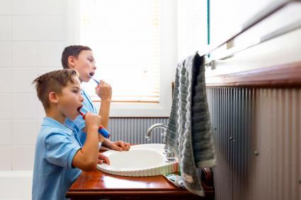 Dos hermanos cepillando los dientes en el baño